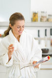 Happy young woman drinking milk in kitchen Stock Photography