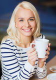 Happy young woman drinking tea or coffee Stock Photography