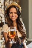 Happy young woman drinking water at bar or pub Stock Photos