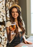Happy young woman drinking water at bar or pub Stock Images