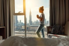 Happy young woman drinks coffee in morning at window Stock Photo