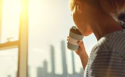 Happy young woman drinks coffee in morning at window stock images