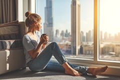 Happy young woman drinks coffee in morning at window Royalty Free Stock Photos