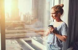 Happy young woman drinks coffee in morning at window Royalty Free Stock Photography