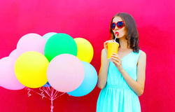 Happy young woman drinks a fruit juice from cup with an air colorful balloons over pink background Royalty Free Stock Photo
