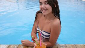 Happy young woman drinks vivid cocktail in blue water of pool at hot sunny day. In summer stock video footage