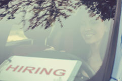 Happy young woman driver inside her car with hiring sign on windshield. Happy woman driver inside her car with hiring sign on windshield Stock Image