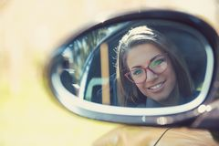 Woman driver looking in the side view mirror of her new car royalty free stock photos