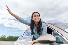Happy young woman driving in car and waving hand Royalty Free Stock Image