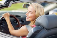 Happy young woman driving convertible car Stock Image