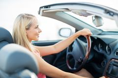 Happy young woman driving convertible car Royalty Free Stock Images