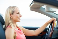 Happy young woman driving convertible car Stock Images