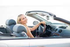 Happy young woman driving convertible car Stock Photography