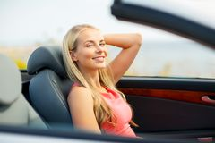 Happy young woman driving convertible car royalty free stock image
