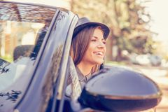 Happy young woman driving convertible on sunny day stock photo