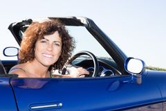 happy young woman driving her convertible top automobile on bright sunny day stock images
