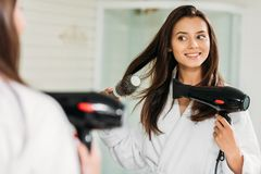 Happy young woman drying hair at mirror. In bathroom stock image