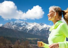 Happy young woman with earphones jogging outdoors Stock Photo