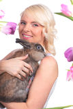 Happy young woman with easter bunny and tulips Royalty Free Stock Images