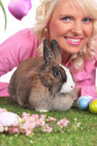 Happy young woman with easter bunny and tulips. Smiling Stock Images