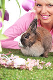 Happy young woman with easter bunny and tulips. Smiling Royalty Free Stock Images