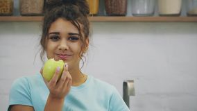 Happy young woman eating apple on kitchen. Diet. dieting concept. Healthy food. Loosing weigh. stock video footage