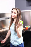 Happy young woman eating apples on kitchen. Happy young woman eating apples on modern kitchen Stock Photo