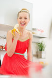 Happy young woman eating banana in kitchen Stock Photography