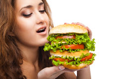 Happy Young Woman Eating big yummy Burger isolated Royalty Free Stock Images