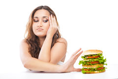 Happy Young Woman Eating big yummy Burger isolated Stock Photography