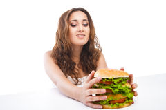 Happy Young Woman Eating big yummy Burger isolated Royalty Free Stock Image