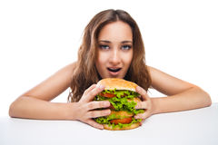 Happy Young Woman Eating big yummy Burger isolated Stock Photo