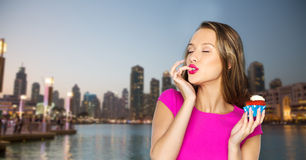 Happy young woman eating birthday cupcake Royalty Free Stock Images