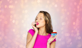 Happy young woman eating birthday cupcake Stock Photos