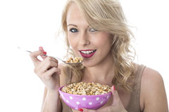 Happy Young Woman Eating Breakfast Cereals Stock Images