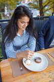 Happy young woman eating cake at outdoors cafe. royalty free stock image