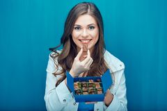 Happy young woman eating chocolate candies. Portrait against blue wall Stock Photo