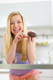 Happy young woman eating chocolate muffin. In kitchen Royalty Free Stock Photography