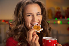Happy young woman eating christmas snacks Stock Photography