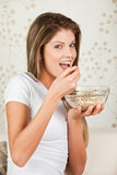 Happy young woman eating cornflakes. At home Stock Photo