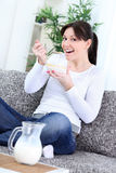 Happy young woman eating cornflakes. At home Royalty Free Stock Photography