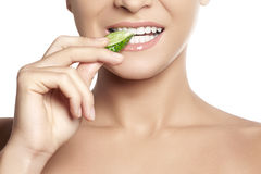Happy young woman eating cucumber. Healthy smile with white teeth. Happy young woman eating cucumber. A close-up of beautiful girl eating cucumber. Healthy smile Stock Photography