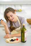 Happy young woman eating fresh cheese and olives Stock Photography