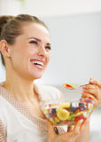 Happy young woman eating fresh fruits salad Stock Images
