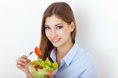 Happy young woman eating a fresh salad Royalty Free Stock Image