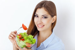 Happy young woman eating a fresh salad Royalty Free Stock Photos