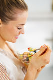 Happy young woman eating fruits salad Stock Photo