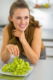 Happy young woman eating grape in kitchen Stock Images