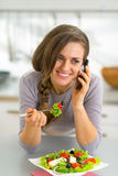 Happy young woman eating greek salad in kitchen Stock Photography