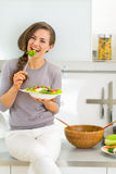 Happy young woman eating greek salad Stock Photos